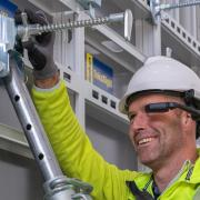 Worker using a head mounted device to adjust the formwork correctly.