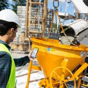 Worker standing in front of the concrete mixer, holding smart phone