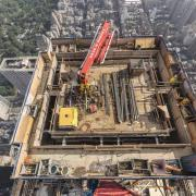 The concrete placing boom climbs crane-independently and casts the core, the slabs and the columns. Foto: Doka